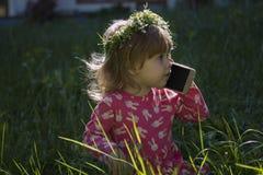 小女孩谈话在手机反对公园绿色在夏天 库存照片