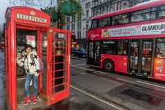 小女孩谈话在电话在电话亭在伦敦 库存照片