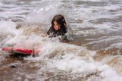 小女孩跌下识别不明飞机委员会浅水区碎波 免版税库存照片