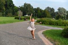 小女孩跳舞的一张正面照片在一张通行证的在一个美丽的绿色公园 免版税库存图片