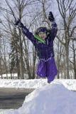 小女孩跳雪堆 免版税库存图片