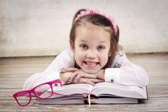小女孩阅读书和微笑 库存照片