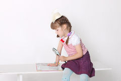 小女孩阅读书,当坐在长凳时 库存照片