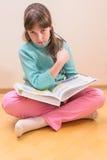 年轻小女孩阅读书 免版税库存照片