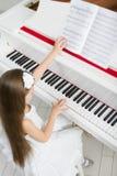 小女孩顶视图弹钢琴的白色礼服的 免版税图库摄影