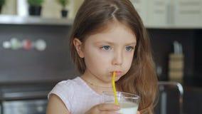 小女孩饮用奶通过从玻璃的秸杆 股票视频