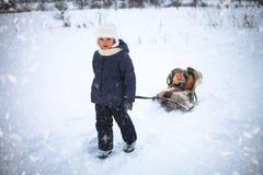 小女孩驾驶雪橇whith在雪的一只红色猫 免版税库存图片