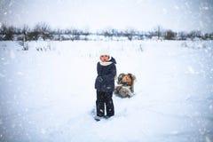 小女孩驾驶雪橇whith在雪的一只红色猫 免版税图库摄影