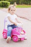 小女孩骑马玩具汽车 免版税库存照片