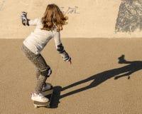 小女孩骑马滑板 免版税库存照片