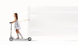 小女孩骑马滑行车 免版税库存照片