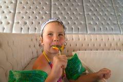 小女孩,在游泳是吃五颜六色的棒棒糖后 库存图片
