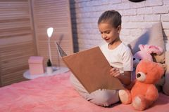 小女孩,孙女在家是阅读书在晚上 免版税库存照片