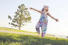 小女孩,弹起,沿草甸跑 免版税库存图片