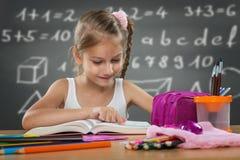 小女孩读书在学校,书面在板材后的工作 免版税库存图片