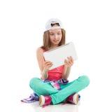小女孩读书某事在一种数字式片剂 免版税库存图片