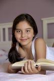 小女孩读书画象在床屋子里 免版税库存照片