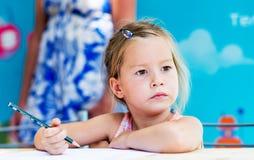 小女孩绘画和作梦 库存图片