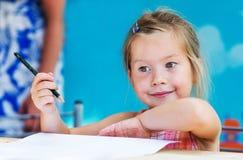小女孩绘画和作梦 库存照片