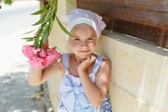 小女孩5年嗅到一朵花的金发碧眼的女人在夏天 免版税库存图片