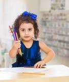 小女孩画在与铅笔的桌上 免版税图库摄影