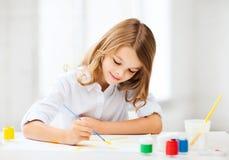 小女孩绘画在学校 库存照片