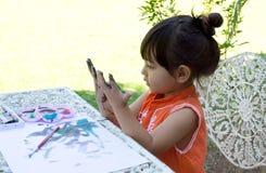 小女孩绘画在庭院里在家 免版税库存照片