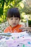 小女孩绘画在庭院里在家 库存照片