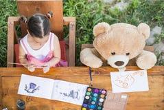 小女孩绘室外与她的玩具熊朋友 库存图片