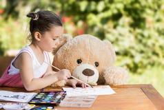 小女孩绘室外与她的玩具熊朋友 图库摄影