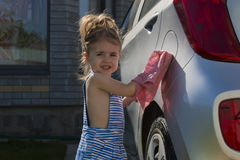 小女孩洗涤汽车 儿童帮助的家庭干净的汽车 库存图片