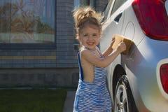 小女孩洗涤汽车 儿童帮助的家庭干净的汽车 免版税库存图片