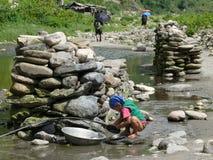 小女孩洗涤盘在河-尼泊尔 免版税库存图片