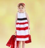 小女孩去购物与红色小包 免版税图库摄影