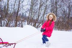 小女孩去的sledding在多雪的冬日 免版税库存图片