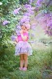 小女孩画象在一个淡紫色庭院里 图库摄影