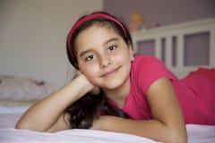 小女孩画象在床屋子里 免版税图库摄影