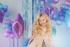 小女孩画象在有很多颜色baloons的一个演播室坐 库存图片
