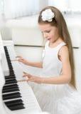 小女孩画象弹钢琴的白色礼服的 免版税库存图片