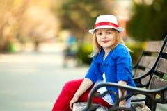 小女孩画象长凳的在公园 免版税库存照片