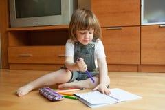 小女孩画,当坐时 免版税库存照片