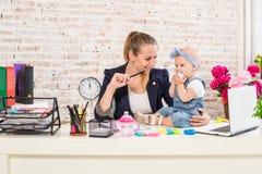 小女实业家计算机前面女孩她家庭水平膝上型计算机妈妈使用塑造视图腰部工作 免版税图库摄影