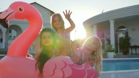 小女朋友在暑假,甜女孩在可膨胀的桃红色火鸟说谎在水池,被损坏的富有的childs附近  影视素材