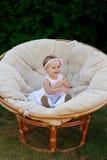 小女婴在一把白色椅子摆在 她愉快地微笑着 免版税库存照片