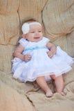 小女婴在一把白色椅子摆在 她愉快地微笑着 免版税库存图片