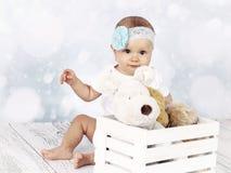 小女婴坐与箱的地板长毛绒戏弄 免版税库存图片