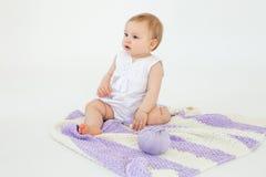 小女婴坐与被隔绝的格子花呢披肩的地板 免版税库存图片