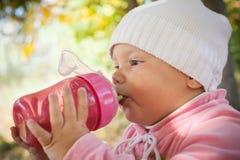 小女婴从桃红色塑料瓶喝 免版税图库摄影