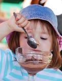 小奶油色吃的eis的女孩 库存照片