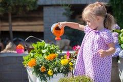 小好女孩浇灌的花用水 免版税库存图片